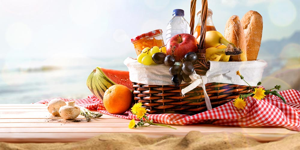 picnic basket filled with food on the beach