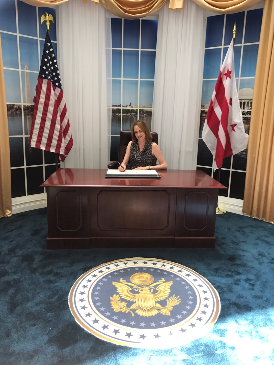 Denise Morton sitting at replica oval office Resolute desk